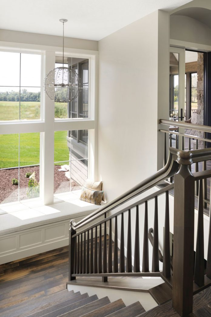 A stairwell in a home on Midwest Home's 2018 Luxury Home Tour that features a landing between floors with a bench and large windows.