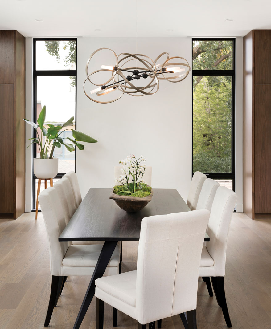 In the main living area, the home's formal dining table sits beneath a contemporary chandelier, in tune with the condo's urban atmosphere. Part of Midwest Home's 2018 Luxury Home Tour.