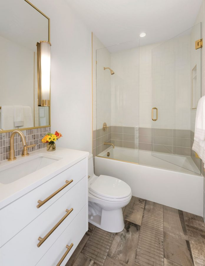 An all white bathroom in a home on Midwest Home's 2018 Luxury Home Tour that shows vanity, toilet, and tub with shower.