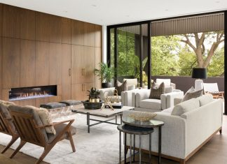 In the open plan living area, entertaining opportunities abound–guests can gather around the gas fireplace or jaunt out onto the balcony for a breath of fresh air. Part of Midwest Home's 2018 Luxury Home Tour.