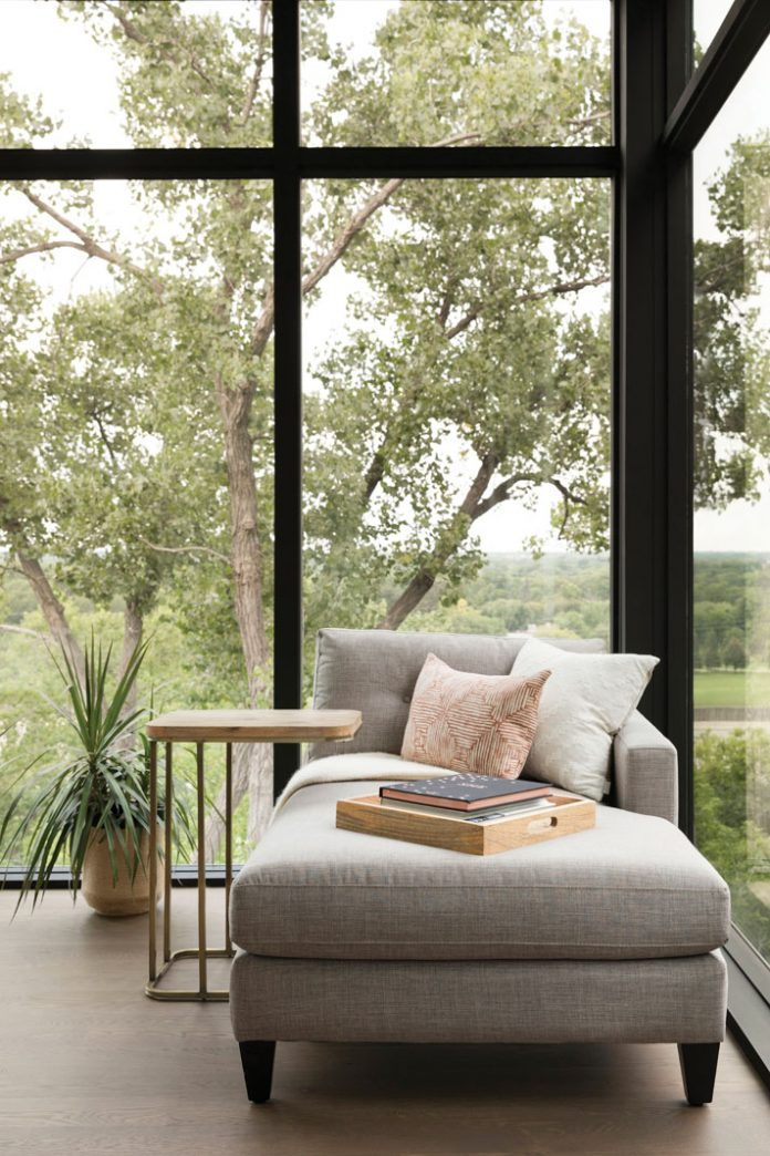 Lounge seating next to a floor-to-ceiling window over looking trees in a home on Midwest Home's 2018 Luxury Home Tour.