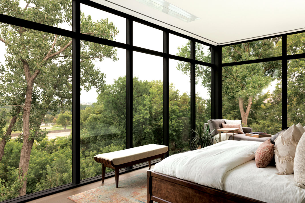 Floor-to-ceiling windows (equipped with retractable shades) in the master bedroom allow for a stunning panoramic view of the surrounding treetops, with glimpses of the Minneapolis skyline visible through the leaves. Part of Midwest Home's 2018 Luxury Home Tour.
