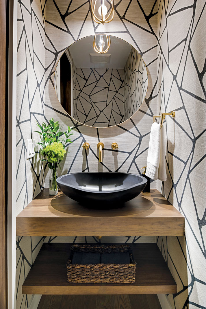 Geometric patterns on the wall and a black stone basin sink create unique textures in a powder room. Part of Midwest Home's 2018 Luxury Home Tour.