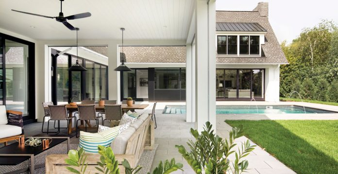 The outdoor patio with seating and pool of a home on Midwest Home's 2018 Luxury Home Tour.