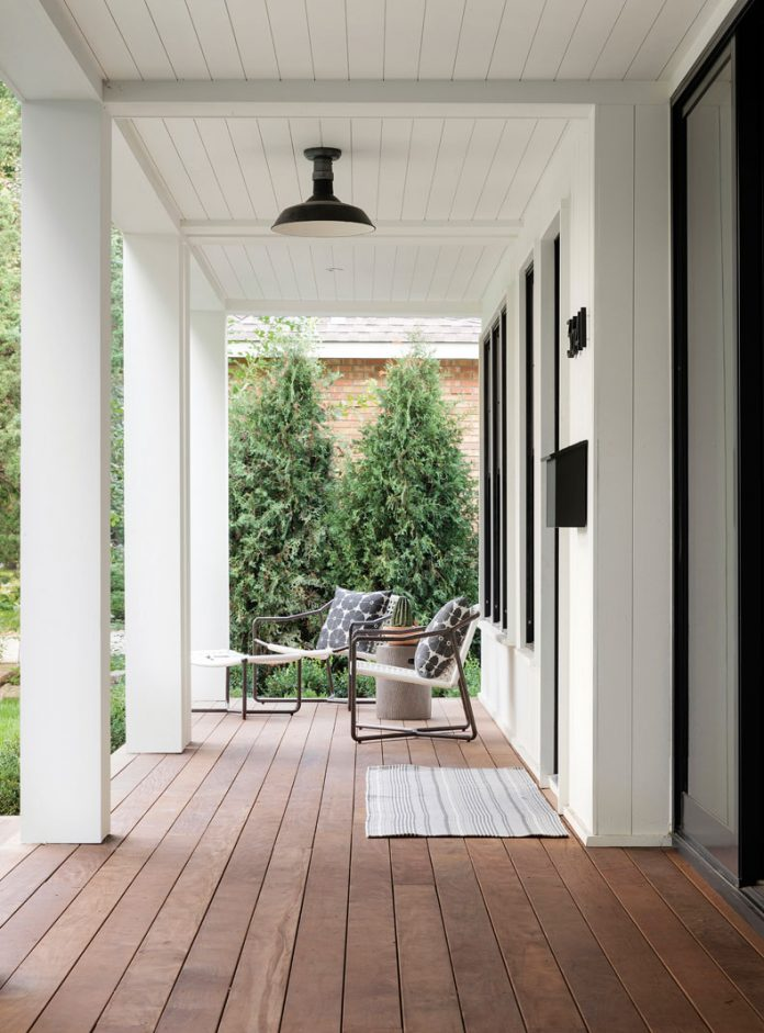 The front porch of a home with seating and pillars at a home on Midwest Home's 2018 Luxury Home Tour.