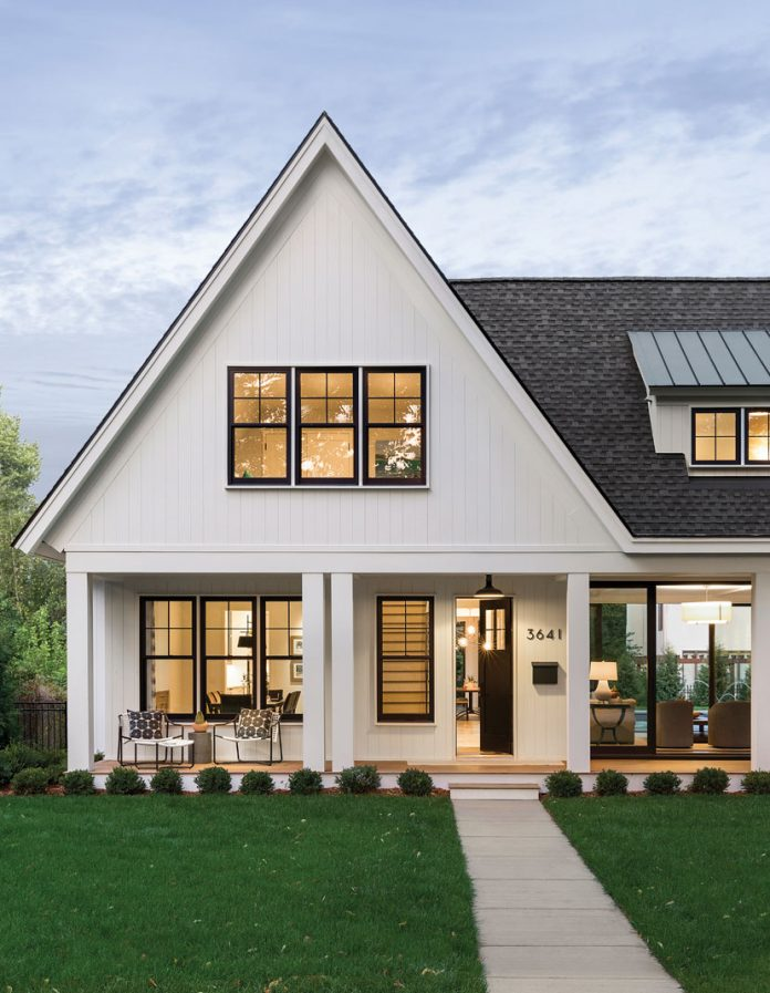 The exterior of a home on Midwest Home's 2018 Luxury Home Tour that shows a white home with large windows, front porch, and green lawn.