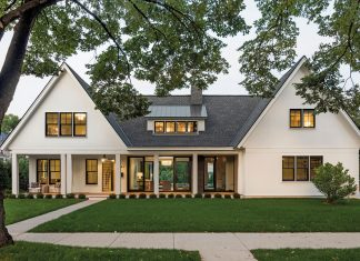The exterior of a home, to which, upon arrival, guests are met with an inviting front porch tucked beneath one of the home's two distinctive gabled pavilions. Part of Midwest Home's 2018 Luxury Home Tour.