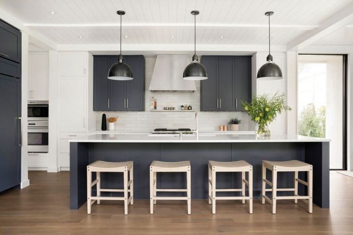 The kitchen in a home on Midwest Home's 2018 Luxury Home Tour that features a center island with seating, hanging lights, and blue cabinetry.