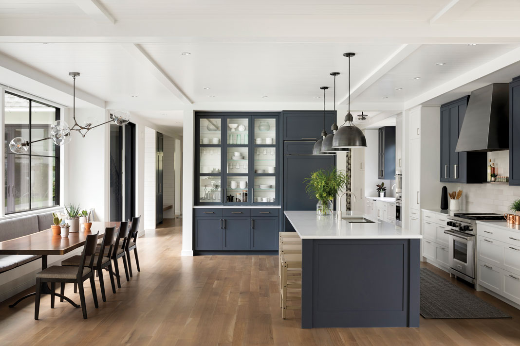 "As the gathering hub of the home, the kitchen offers plentiful space for the entire family, and the Shaker-style cabinetry and harvest table situated beneath a contemporary chandelier emphasize the house's ""contemporary cottage"" aesthetic. Part of Midwest Home's 2018 Luxury Home Tour."