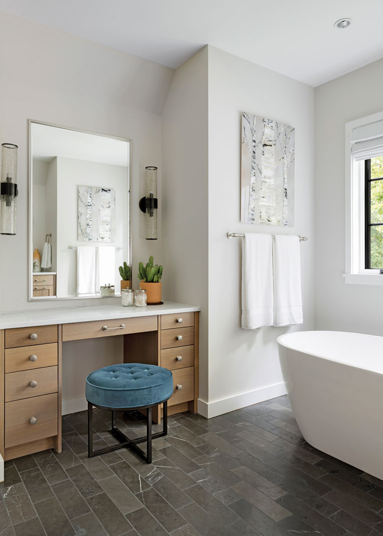 A luxurious spa bath acts as the focal point of the master bathroom, while white oak cabinetry and a beautiful vanity tucked in the corner add charm and elegance. Part of Midwest Home's 2018 Luxury Home Tour.