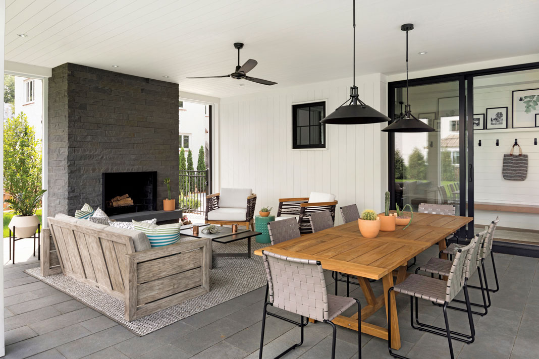 Located beneath one of the home's pavilions is a three-season porch that features retractable screens, a stone wood-burning fireplace, and a variety of seating options. Part of Midwest Home's 2018 Luxury Home Tour.