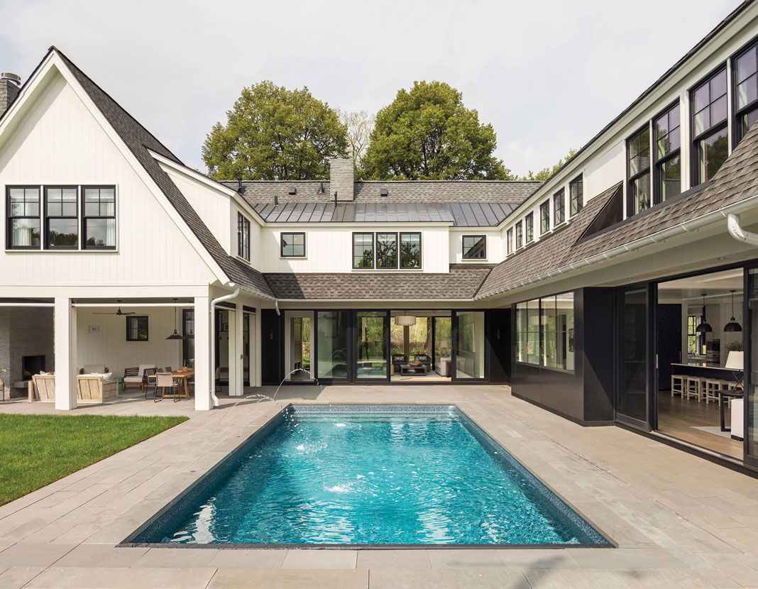 Perhaps the most memorable elements of the home are its U-shape–the house wraps around the swimming pool and patio in the backyard–and its steep rooflines and classic white exterior, which create a modern-yet-traditional cottage motif. Part of Midwest Home's 2018 Luxury Home Tour.