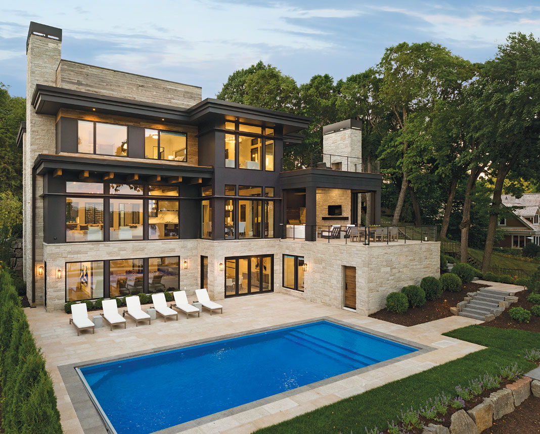 The five-bedroom, seven-bathroom home, as viewed from the lakeside, offers a plethora of outdoor entertaining options such as a sizable pool and large patio. Part of Midwest Home's 2018 Luxury Home Tour.
