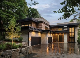 "Built by Stonewood, LLC, this Orono home's ""mountain-modern"" exterior combines a contemporary aesthetic with rustic materials, such as reclaimed barn-wood siding paired with dark metal accents. Featured on Midwest Home's 2018 Luxury Home Tour."