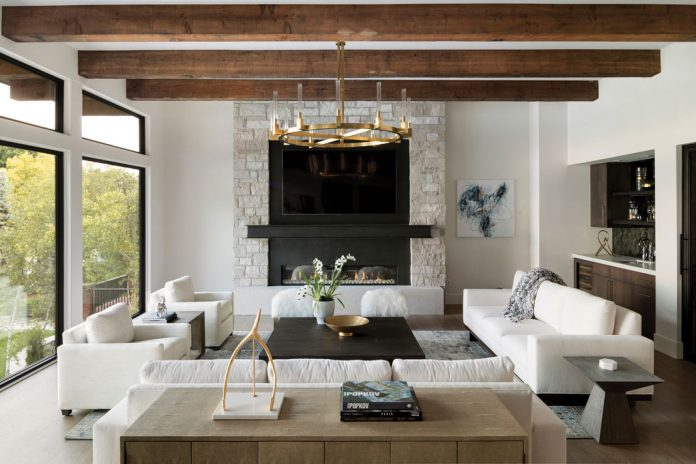 A living room with white seating below a chandelier, and a fireplace on the back wall. Part of Midwest Home's 2018 Luxury Home Tour.