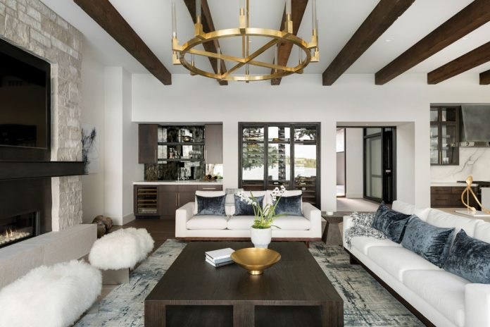 A great room with exposed beams, white seating, and a chandelier hanging above. Part of Midwest Home's 2018 Luxury Home Tour.