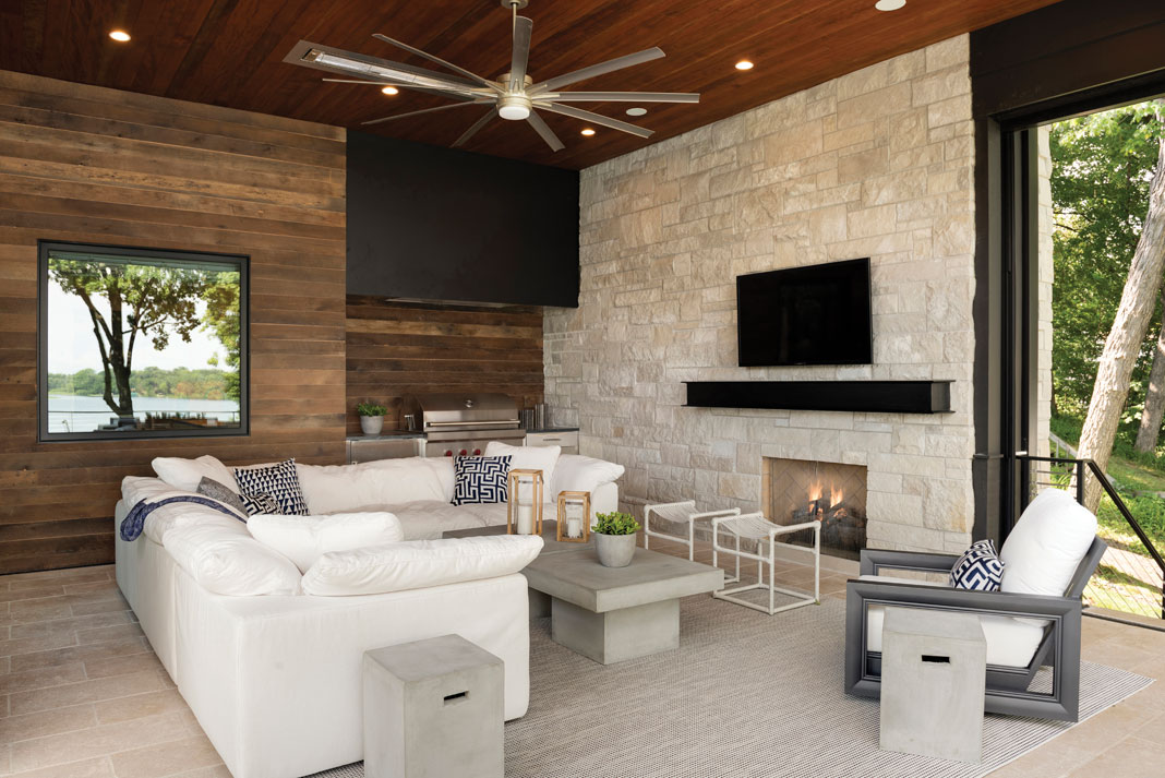 The convertible porch, also accessible from the kitchen, includes a wood-burning fireplace and automated screens and shades for optimized comfort throughout the seasons. Part of Midwest Home's 2018 Luxury Home Tour.