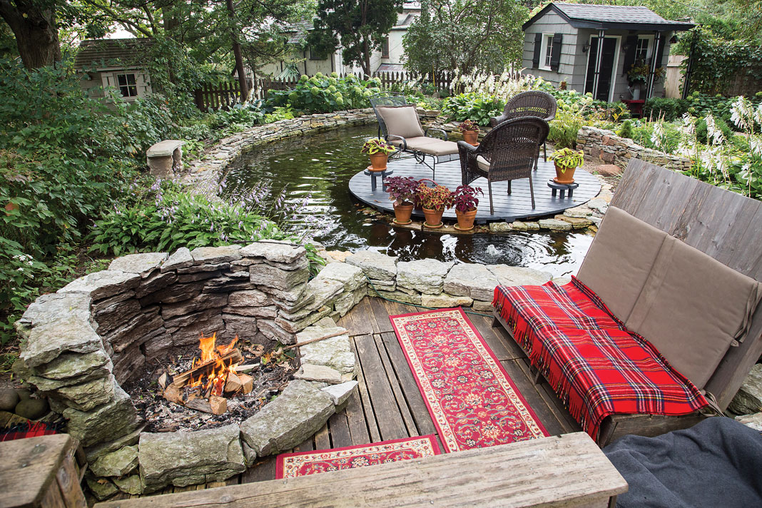 An island-like seating area set within the 3,000-gallon pond and a stone fire pit complete with its own cozy pallet seating offer additional spaces to relax in this luxurious backyard oasis.