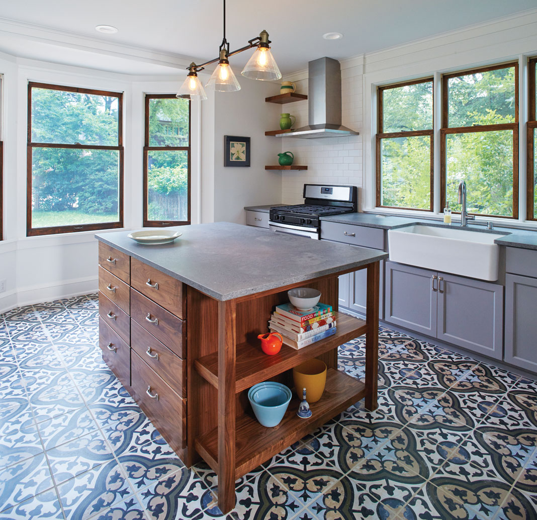 A kitchen with center island, hanging lights, patterned floor, sink, and gray cabinetry.