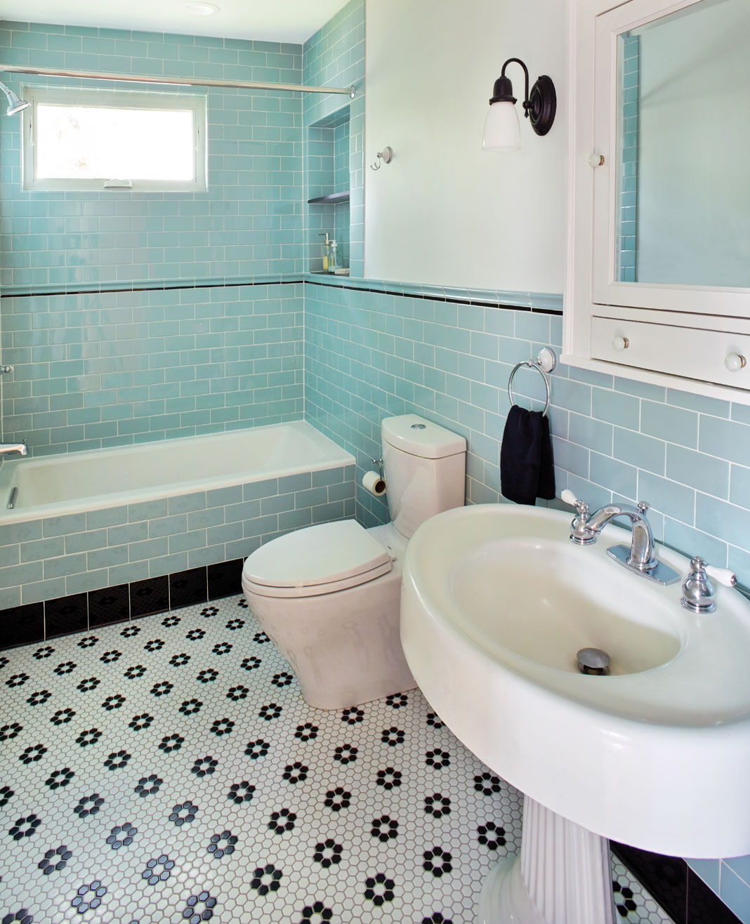 A newly-renovated master bath featuring pale blue subway tile walls.