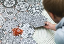 Person laying patterned floor titled