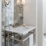 A bathroom with mirrored tiles, white sink and wall sconce light.