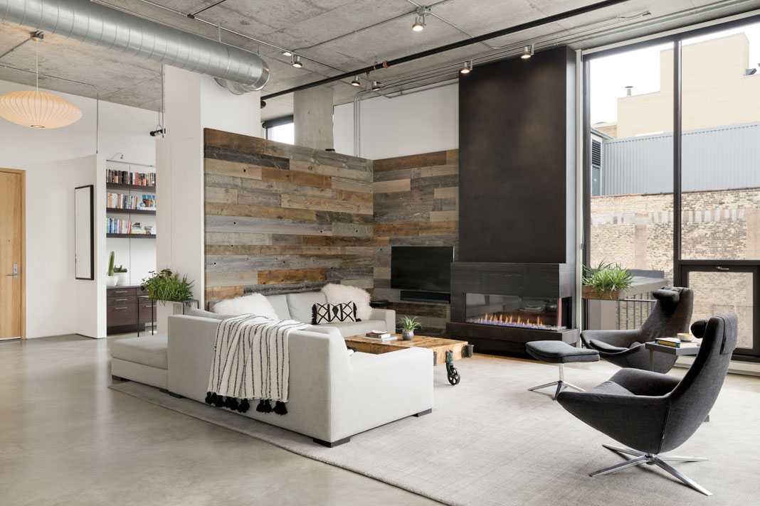 A reclaimed barn wood wall and floor-to-ceiling blackened steel fireplace add texture to the living room's interiors while blending seamlessly with the views of surrounding mill buildings.