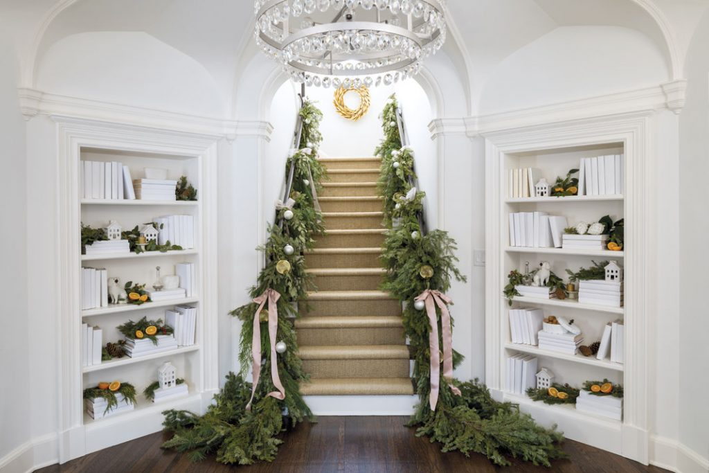 The foyer's sweeping staircase, decked with evergreens and citrus, will welcome the family home.