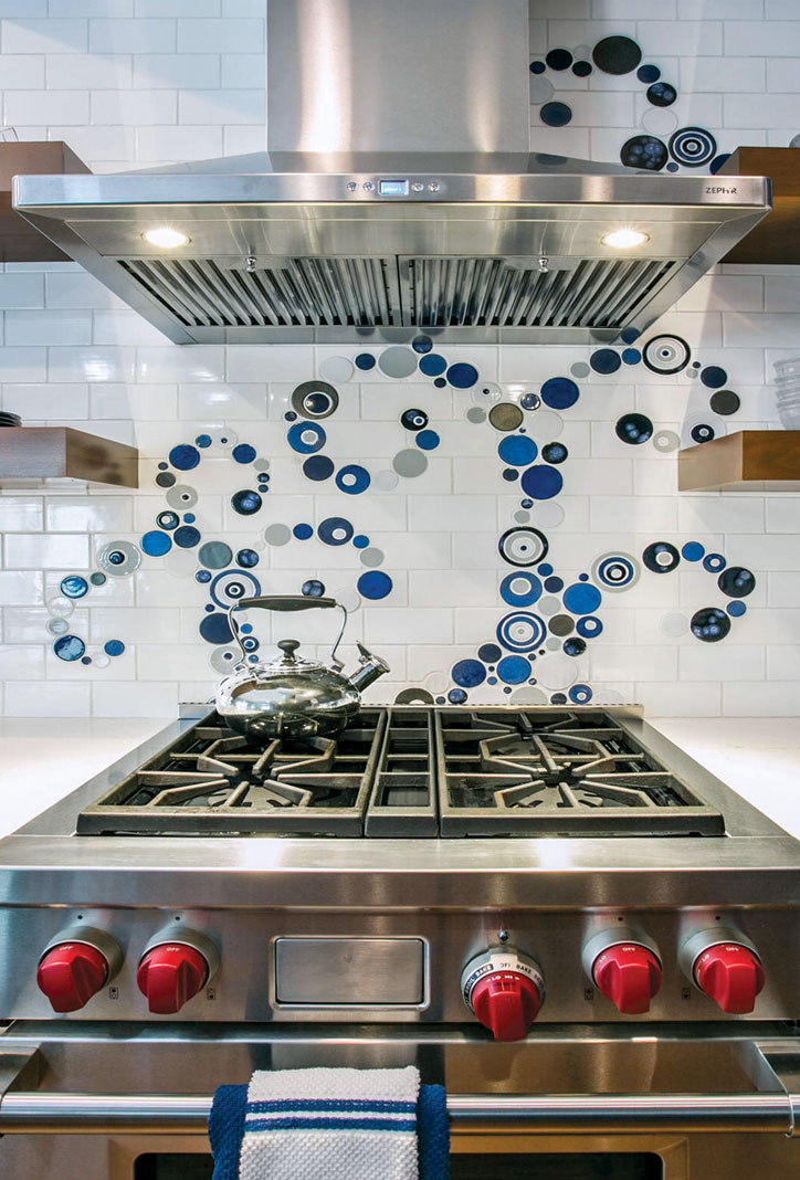 A stainless steel oven and range hood with accompanying subway tile backsplash that also features a custom design of blue and gray bubbles.
