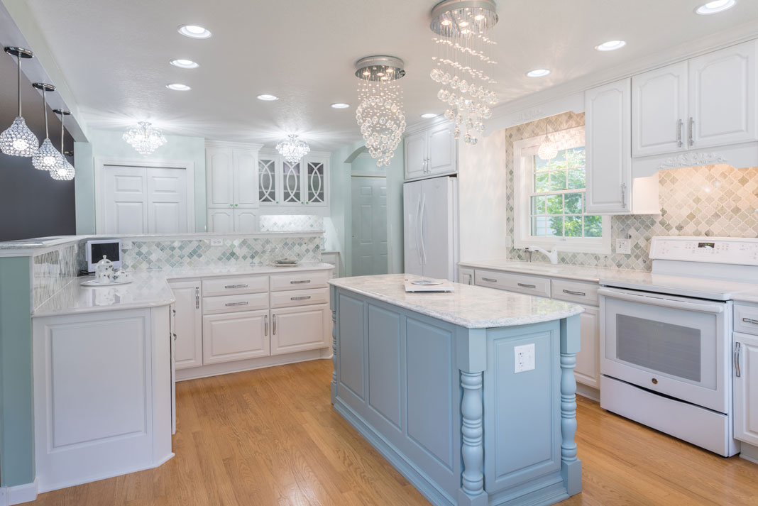 A kitchen distinguished by its soft, baby blue and seafoam green aesthetic, a multicolored backsplash, scroll work appliques, and glossy, marble countertops.