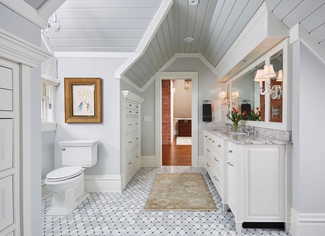 An all white bathroom a double sink vanity, marble shower, mosaic flooring, and heated floors.