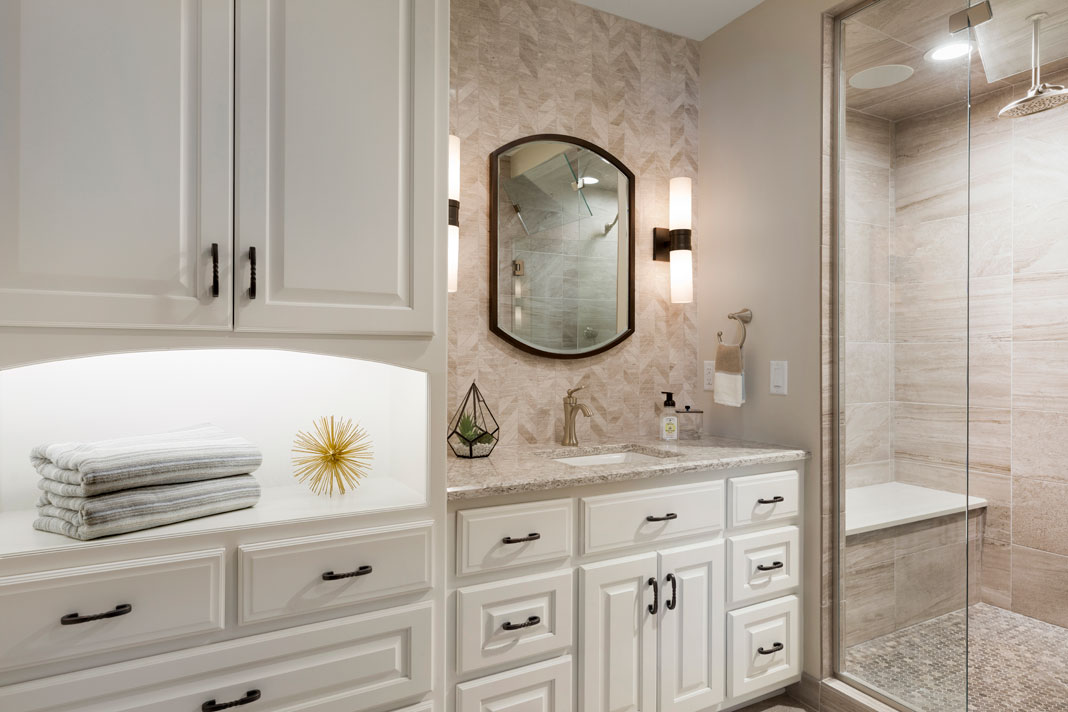 A renovated bathroom that features increased storage, a steam shower, and white vanity with sconce lights.