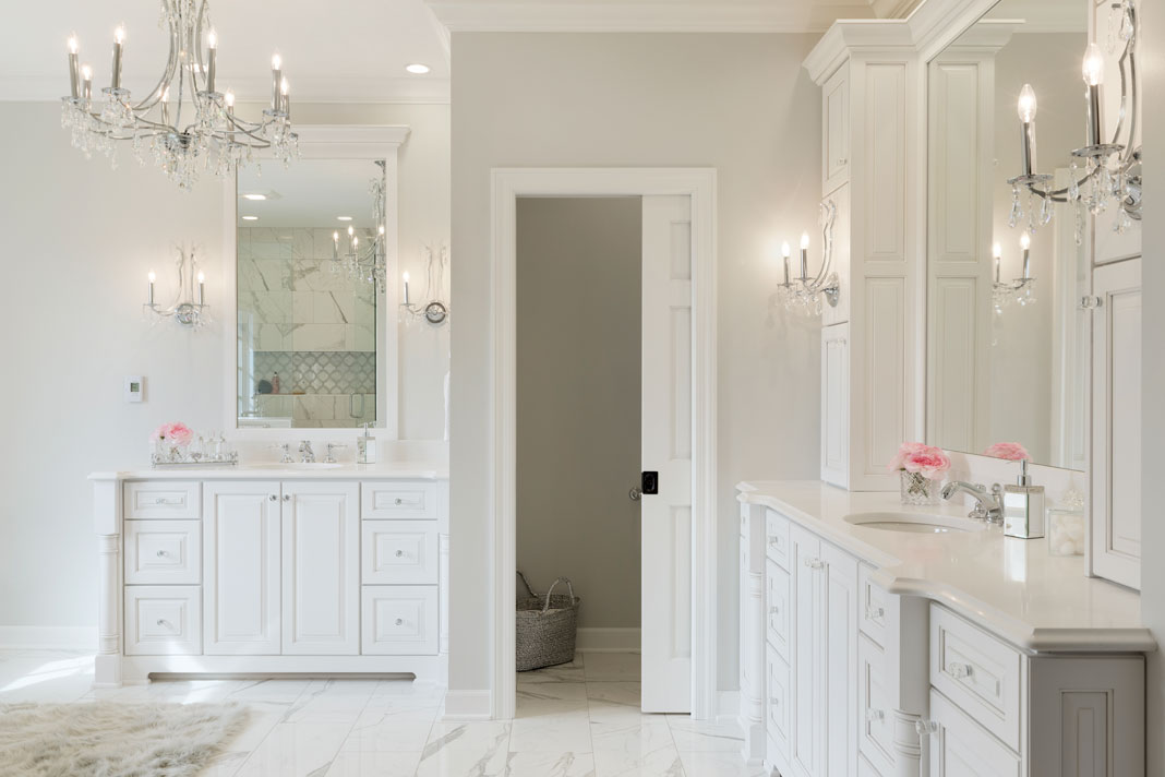 An all white bathroom featuring a double bowl vanity, frameless shower, and lots of storage place.