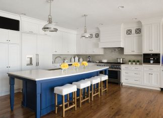 A wood floor kitchen with white cabinetry and a pop of blue paint on the island.