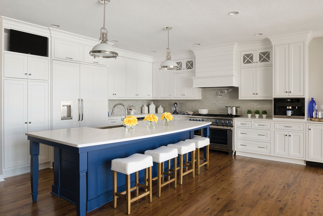 A Wood Floor Kitchen With White Cabinetry And Pop Of Blue Paint On The Island