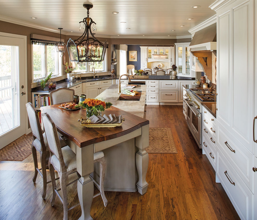 A ornamental kitchen with wood floors, white cabinetry, and dark countertops.