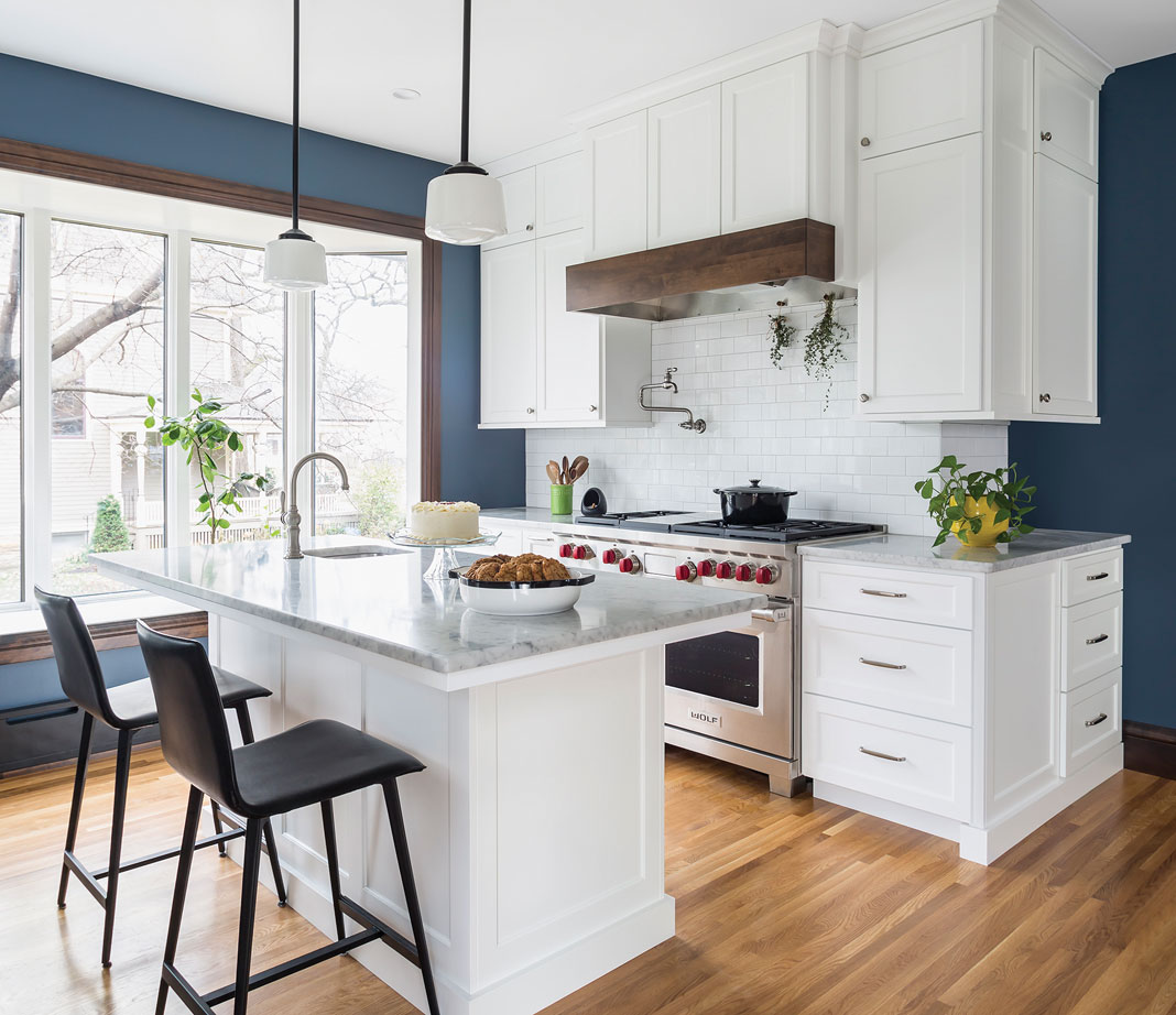 A kitchen with wood flooring, white cabinetry, stainless steel appliances, and a blue accent wall.