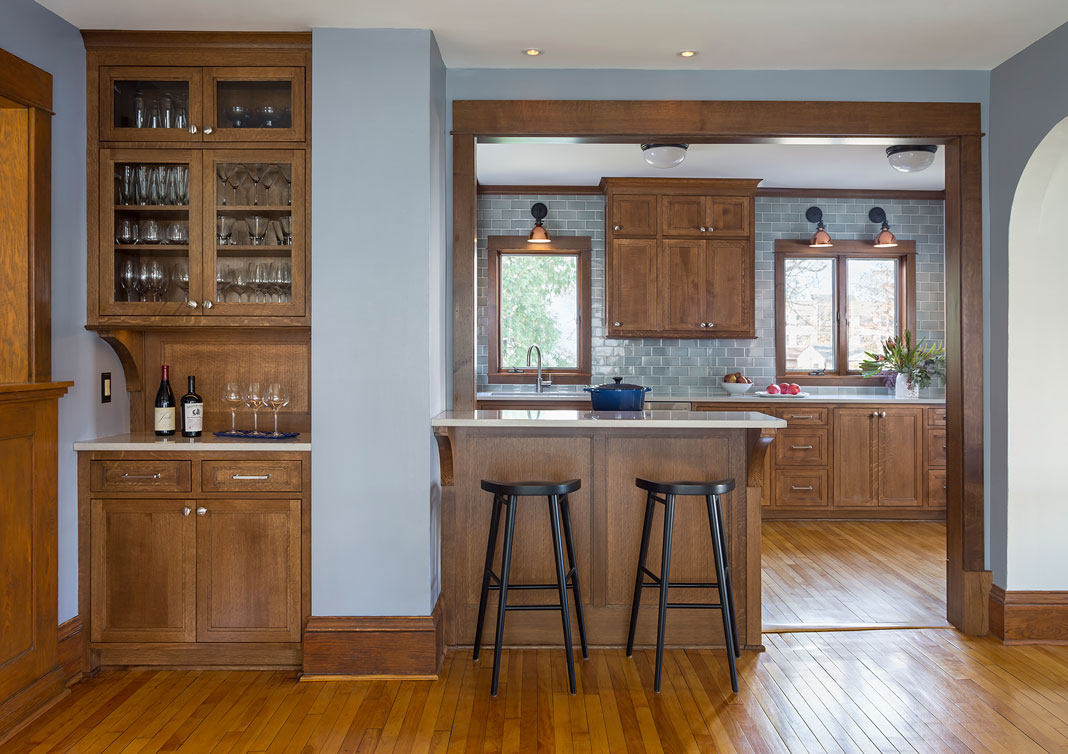 A kitchen with gray blue Sonoma tiles, eat-in counter, sconces, and more.