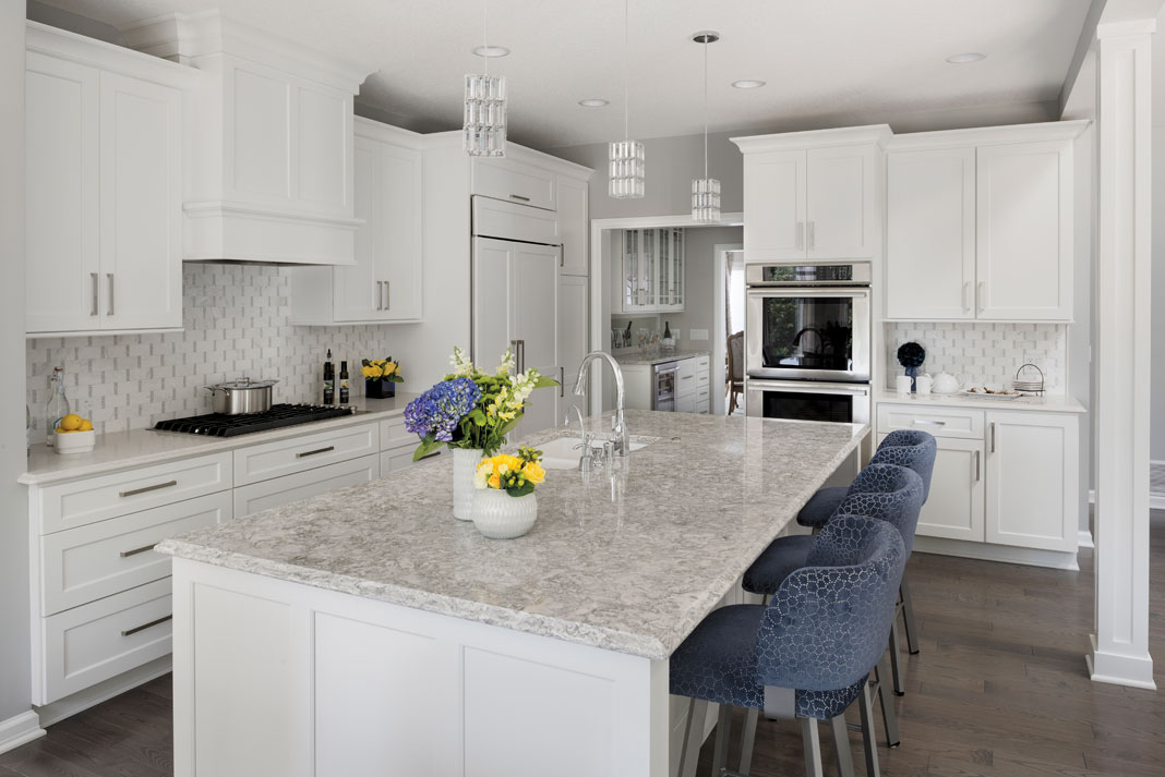 An elegant kitchen with wood floors, marble countertops, and white cabinetry.