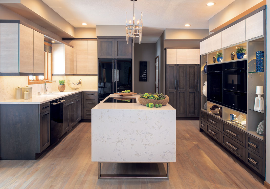 A kitchen with oak flooring, black glass appliances, and two tone cabinets.