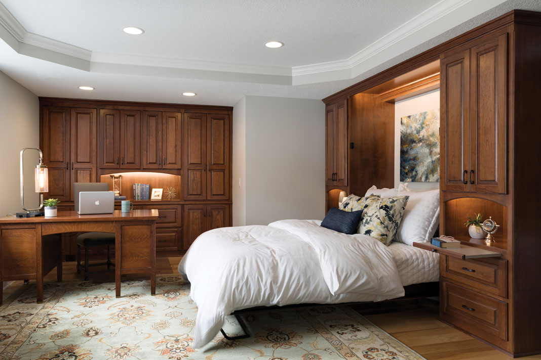 A large bedroom with a pullout Murphy bed nestled between custom, floor-to-ceiling storage areas and below a painting.