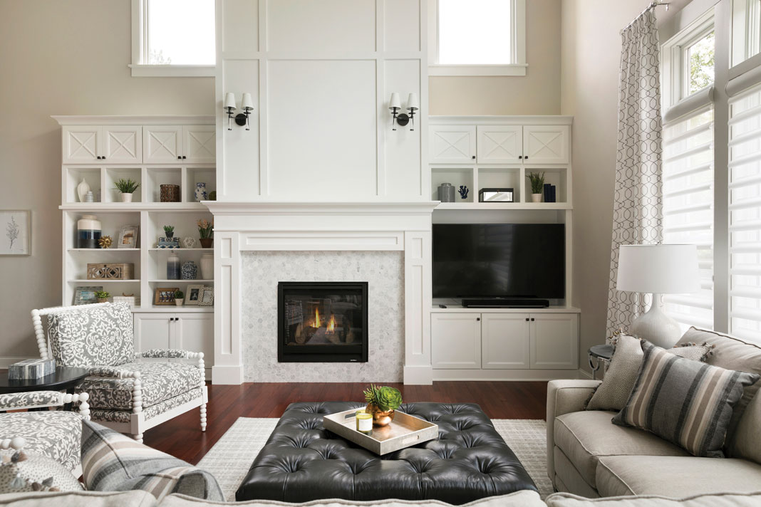 "A spacious living room with a two-story, floor-to-ceiling paneled fireplace with ""X"" patterned cabinetry and sconces."