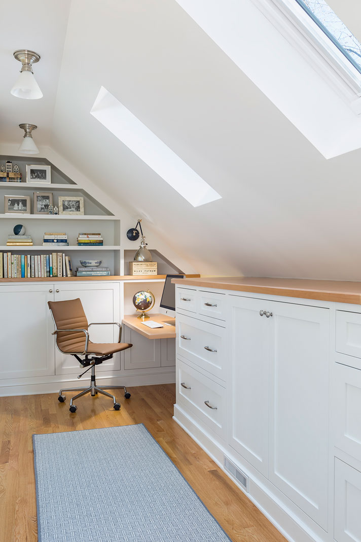 A renovated room that features custom white cabinets, two Velux skylights, open shelves, and a small desk area.