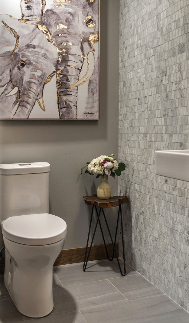 A small, renovated bathroom that features an accent wall made from mosaic Carara marble tiles, small table with with a vase of flowers on top, toilet, and elephant painting.