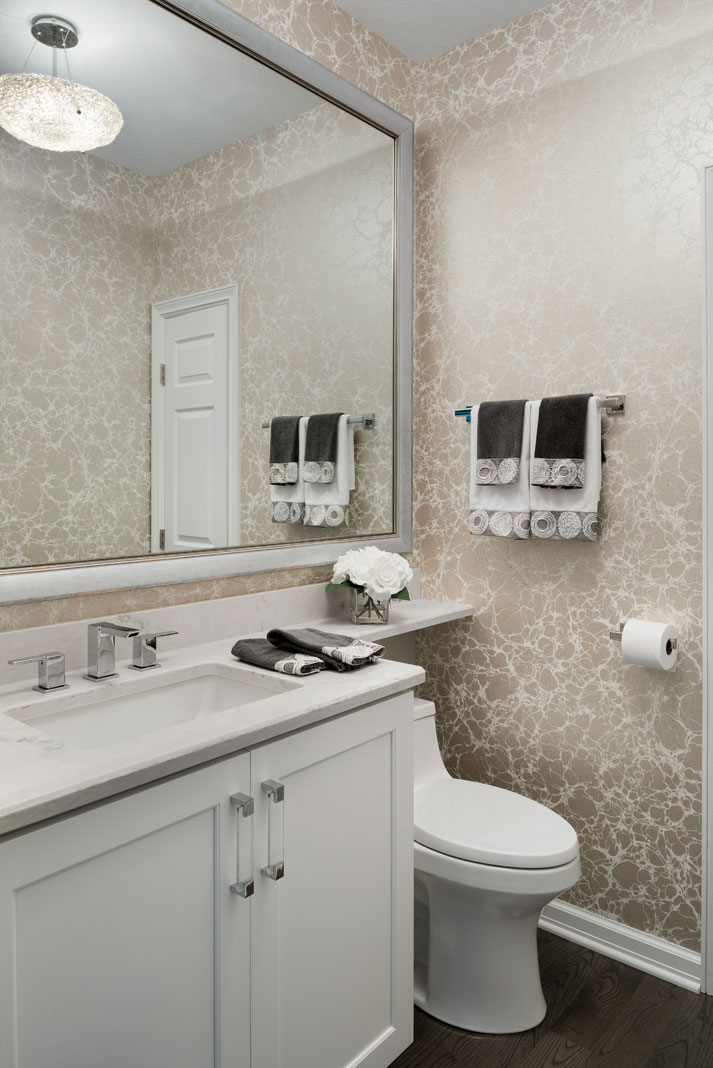 A renovated bathroom that shows a low-tank toilet and large mirror above an all white vanity.