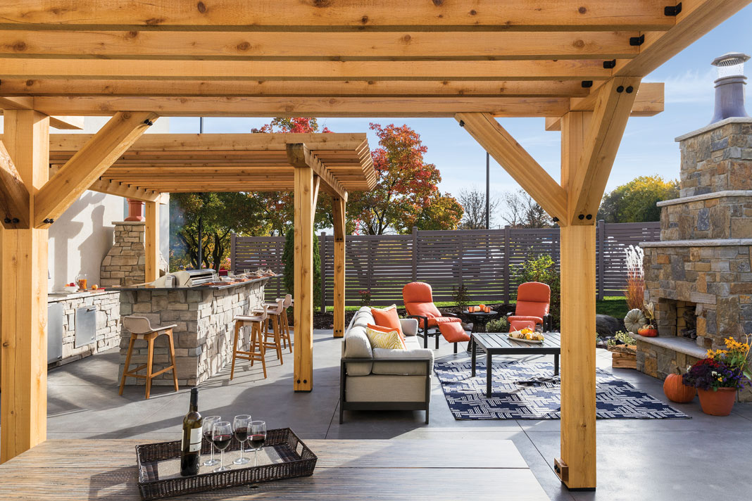 An outdoor patio with beige and orange seating surrounding a table, stone fireplace, and pergolas.