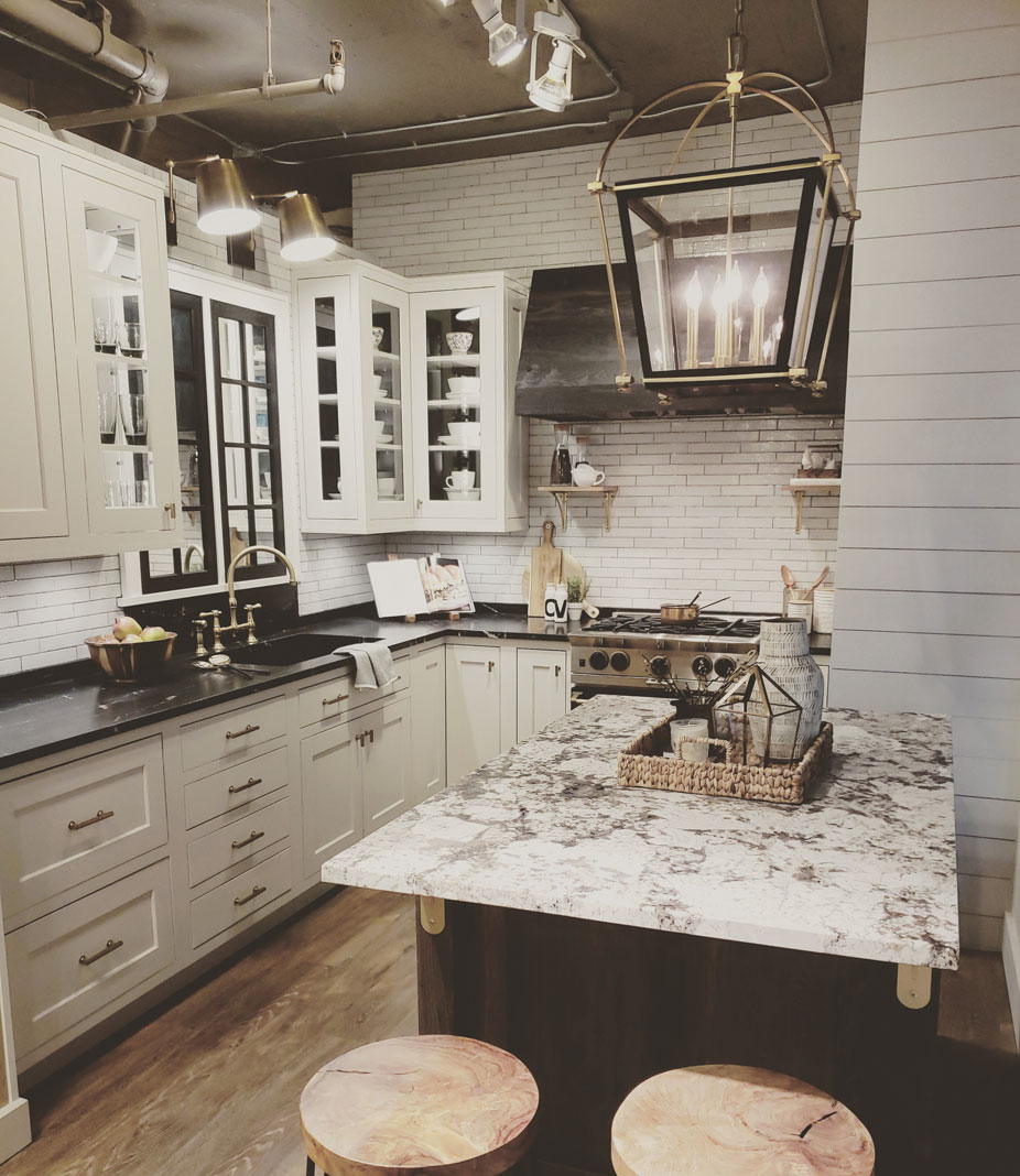 A farmhouse-style kitchen with Via Lattea granite, black, rustic, patina oak cabinetry, lime-washed, vinyl wood plank floors, and a custom-designed hood set against glossy, brick-like tile that shines among a matte trim and the latest in kitchen appliances.