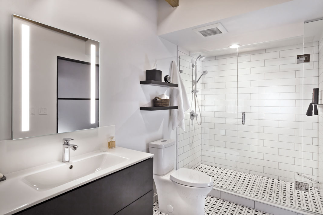 An industrial bathroom with natural wood, black accents, and splashes of white. Pictured is a vanity, toilet, and glass shower.