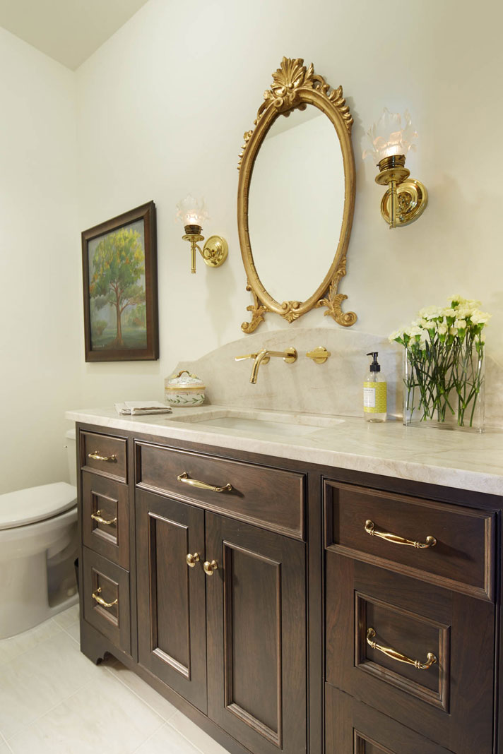 A renovated bathroom that features a marble and glass shower, refurbished, antique sconce, and a grand, gold-framed mirror above the vanity.