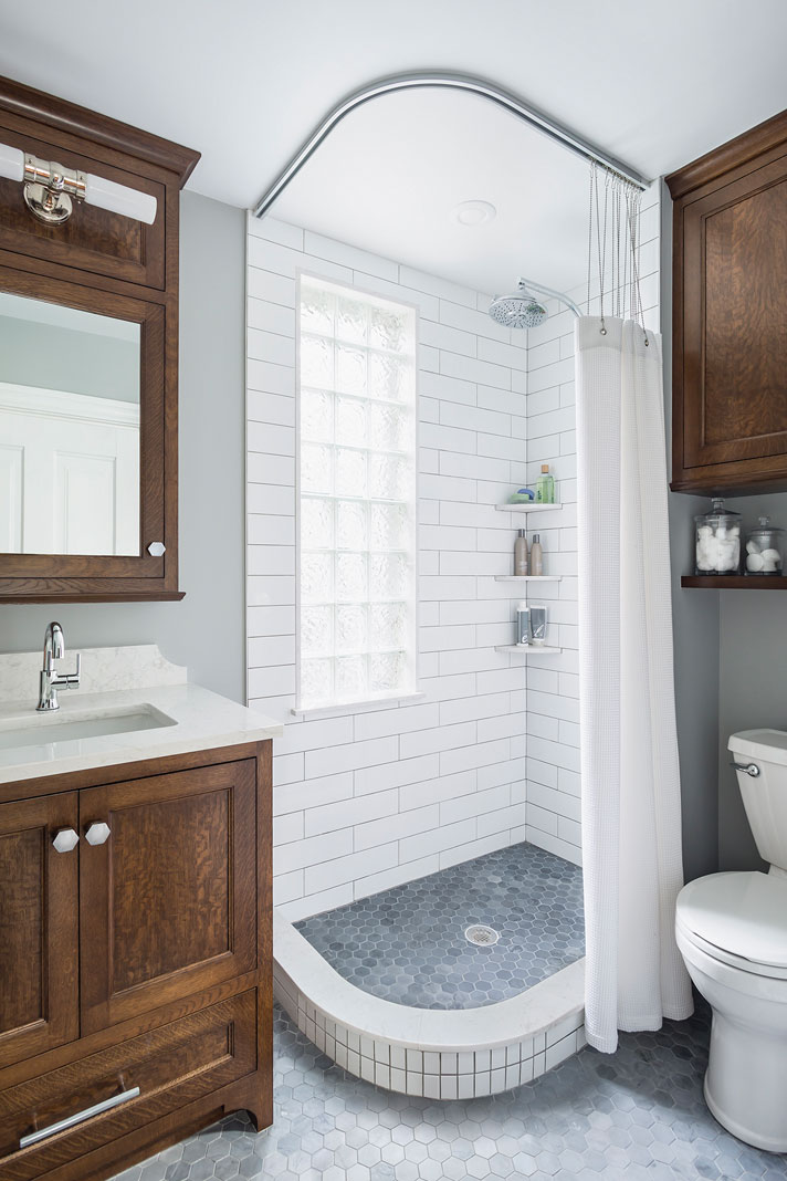 A renovated bathroom that features a floor-to-ceiling shower, space-creating cabinets and vanities, and polished chrome fixtures.